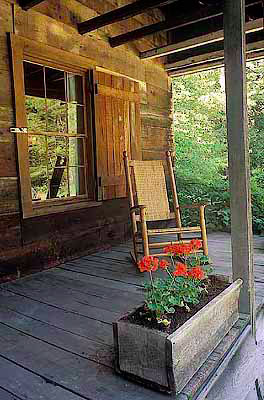 NC: Transylvania County, Pisgah National Forest, Davidson River Area, The Cradle of Forestry In America, Front porch of log cabin; begonias, rocking chair [Ask for #212.207.]