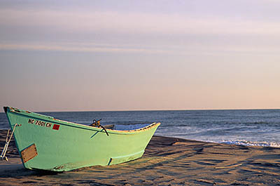 NC: Dare County, The Outer Banks, Hatteras Island, Rodanthe, Morning sun hits a beached fishing boat [Ask for #224.413.]