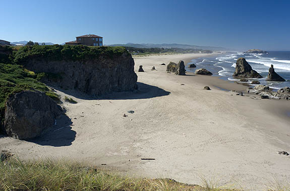 OR: Coos County, Bandon Area, South Beaches, Face Rock State Wayside, House sits atop sheer rock cliffs with a wide sandy beach below, spotted with large hoodoos [Ask for #274.356.]