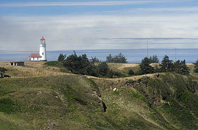OR: South Coast Region, Curry County, North Coast, Cape Blanco Area, Cape Blanco State Park, View of the Cape Blanco Lighthouse atop grassy cliffs as fog rolls in. [Ask for #274.683.]