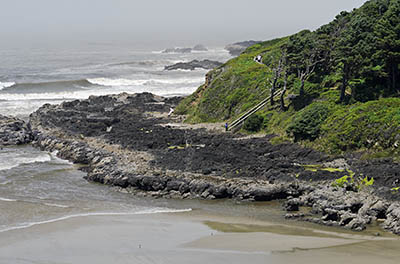 OR: South Coast Region, Lane County, Pacific Coast, Cape Perpetua Area, Cape Perpetua National Scenic Area, Cooks Chasm Viewpoint, A path descends on stairs to a sandy beach in a remote cove, as fog rolls in [Ask for #276.A42.]